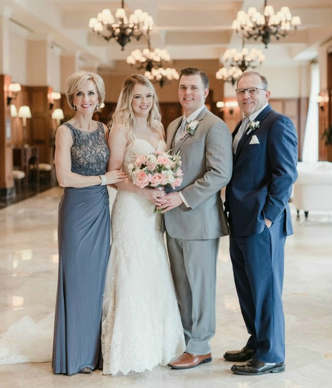 mother of the bride wearing pewter lace gown standing with bride, groom, father of the bride
