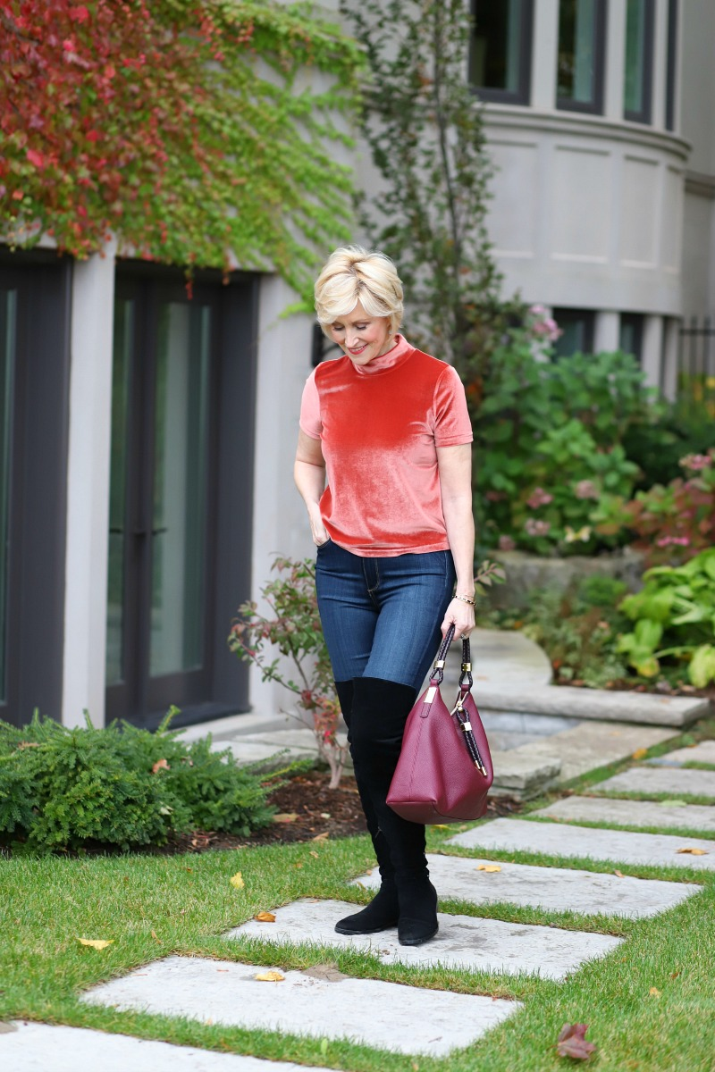 Fashion blogger Deborah Boland of Fabulous After 40 wearing a velvet tee and thigh high suede boots.