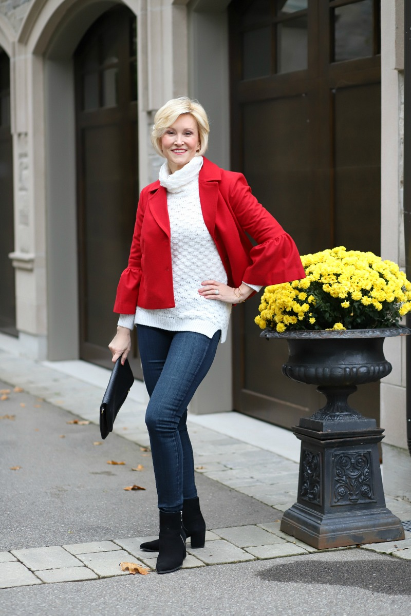 Deborah Boland Short red jacket with ruffle cuff sleeves and a sweater and jeans