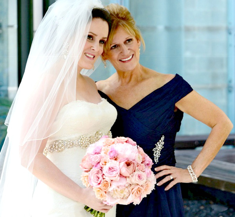 Mother of the bride in royal blue satin gown with sparkly waist broach standing with bride