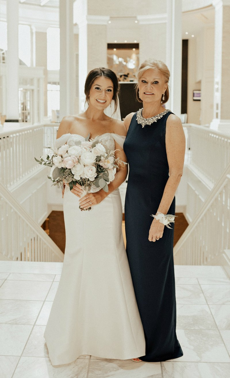 Mother of the bride in navy gown with jewel encrusted neckline standing beside bride