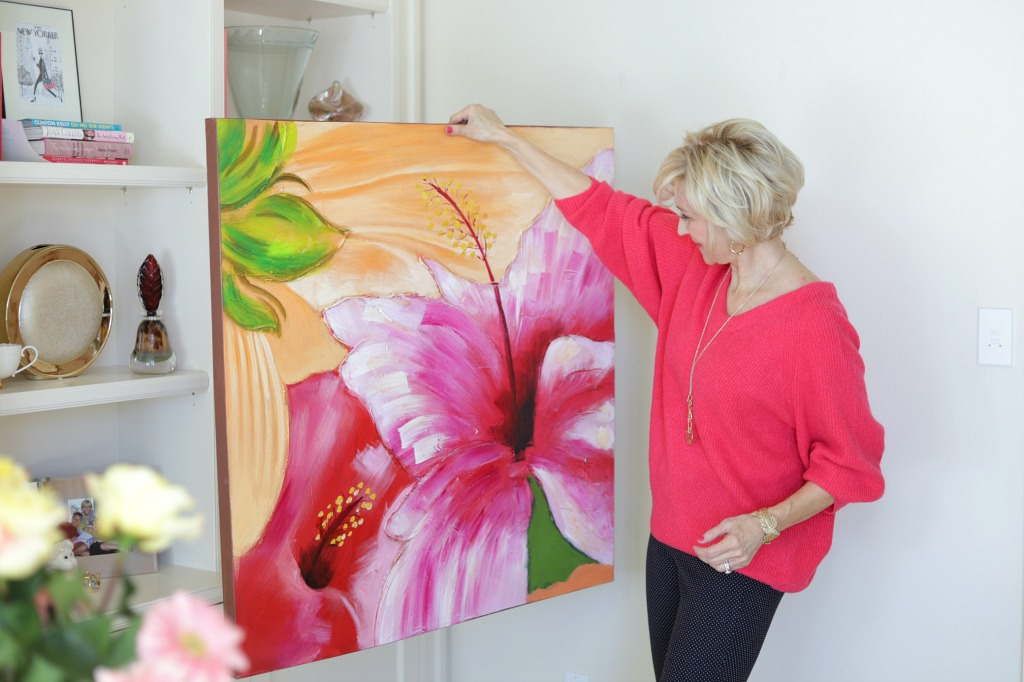woman in pink oversized sweater holding up and looking at floral painting
